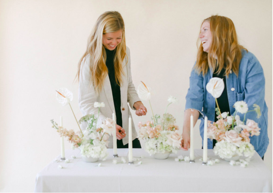 two women behind table, beautiful , modern flowers, florists, taper candles, neutral background